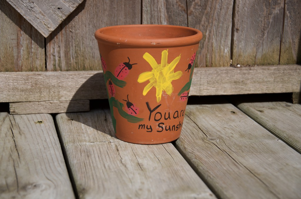 a clay flower pot with thumb print ladybugs, a sun, and a quote