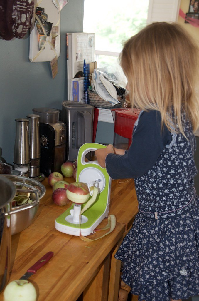 Child using an apple peeler to peel apples